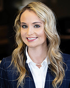 A headshot photo of a woman wearing a navy blue suit jacket