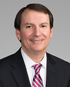 A headshot photo of a man wearing a suit and tie