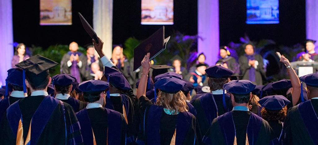 Graduates in purple graduation hats and robes hold up their diplomas