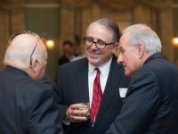 A man smiles as he talks to two other men