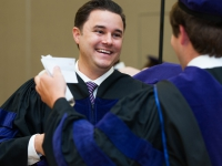 A male student wears a graduation robe and smiles