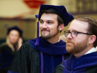 Two male students wearing graduation attire smile for a photo