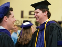 Two male students wearing graduation attire smile