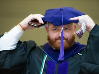 A male student wears a graduation robe and cap and smiles