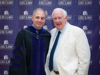 Two men smile for a photo with the LSU Law logo in the background