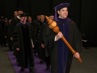 A male student wearing graduation attire carries a wooden mace