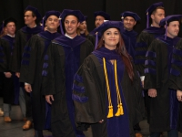 Students wearing graduation attire smile