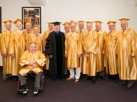A group of men wearing gold robes poses for a photo with a man wearing a black robe