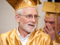 A man wearing a gold graduation cap and gown smiles