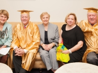 Men wearing a gold graduation cap and gown smile seated next to women