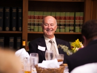 A man wearing a suit and tie is seated at a table and smiles