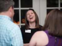 A woman laughs as she talks to a man and a woman