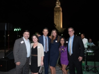 Six people pose for a photo with the Louisiana state capitol in the background.