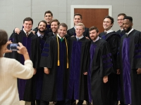 A group of students wearing graduation attire smile for a photo