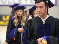A male student wears a graduation robe and cap and looks to the left