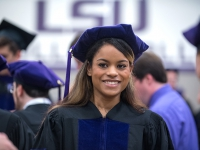 A female student wears a graduation robe and cap and smiles