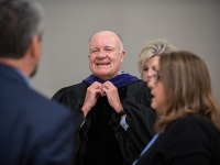 A man smiles as he put on his graduation attire