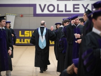 A man gives a high-five to a student wearing graduation attire