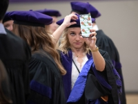 A female student wears a graduation robe and cap and looks at her phone