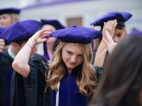 A female student wears a graduation robe and cap