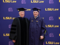 Two men wearing graduation robes and caps smile with the LSU Law logo in the background