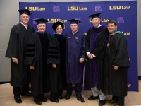 A group of people wearing graduation robes and caps smile with the LSU Law logo in the background