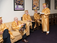 A group of men wearing gold robes talk to each other