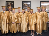 A group of people wearing gold robes poses for a photo