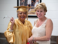 A woman wearing a gold robe poses for a photo with a woman