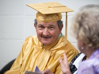 A man wearing a gold robe smiles for a photo