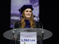 A female student wearing graduation attire speaks at a podium