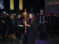 A female student wearing graduation attire carries a wooden mace