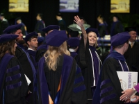Students wearing graduation attire smile and wave