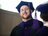A male student wearing graduation attire smiles