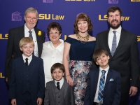 A group photo of seven people wearing semi-formal attire with the LSU Law logo in the background