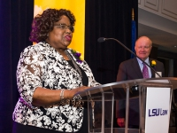 A woman talks at a podium with purple and gold banners in the background