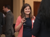 A female student holds a glass of wine and smiles as she talks to a person