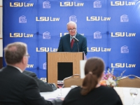 A man wearing a suit and tie speaks at a podium with the LSU Law logo in the background