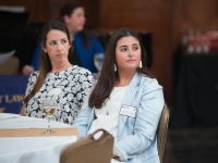 Two female students sit at a table and look on