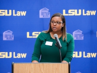 A female student wearing a green dress speaks at a podium with the LSU Law logo in the background