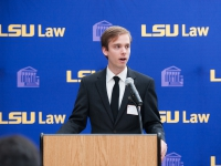 A male student wearing a suit and tie speaks at a podium with the LSU Law logo in the background
