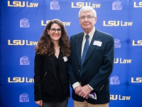 A female student and a man pose for a photo with the LSU Law logo in the background