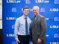 A male student and a man pose for a photo with the LSU Law logo in the background