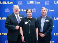 A female student and two men pose for a photo with the LSU Law logo in the background