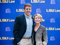 A male student and a woman pose for a photo with the LSU Law logo in the background