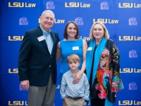 Four people pose for a photo with the LSU Law logo in the background