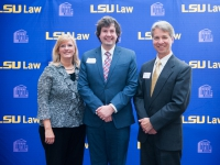 A male student and a man and a woman pose for a photo with the LSU Law logo in the background