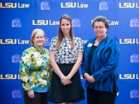 A female student and a two women pose for a photo with the LSU Law logo in the background