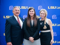 A female student and a man and a woman pose for a photo with the LSU Law logo in the background