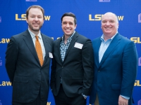 A male student and two men pose for a photo with the LSU Law logo in the background